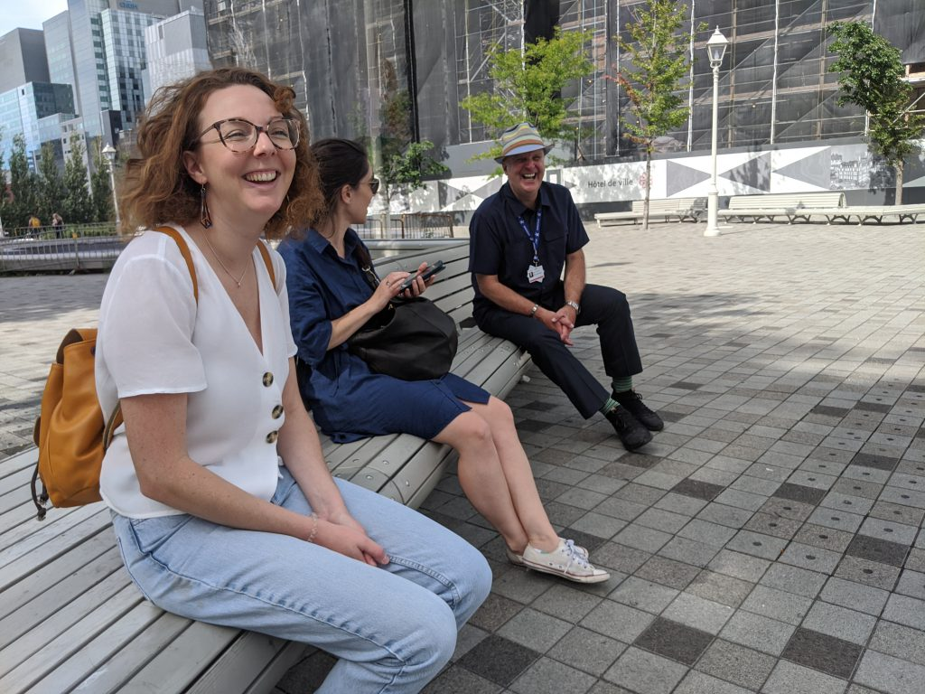 Two young women sit on a bench in Old Montréal with their professional guide sporting his City of Montréal permit