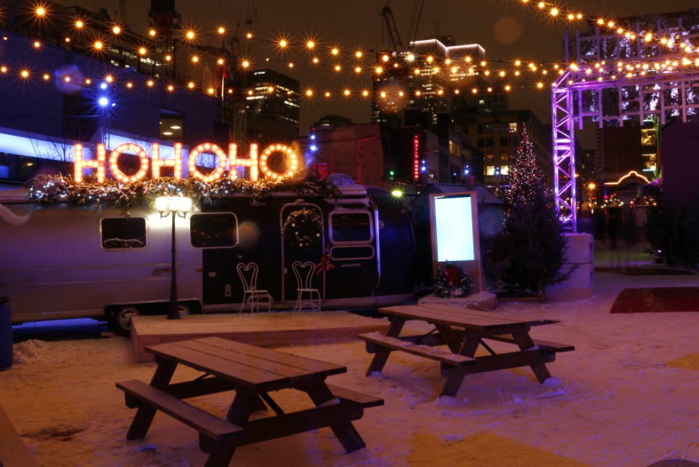Festive lighting, picnic tables, and a HOHOHO sign atop a vintage Winnebago at the Winter Gardens