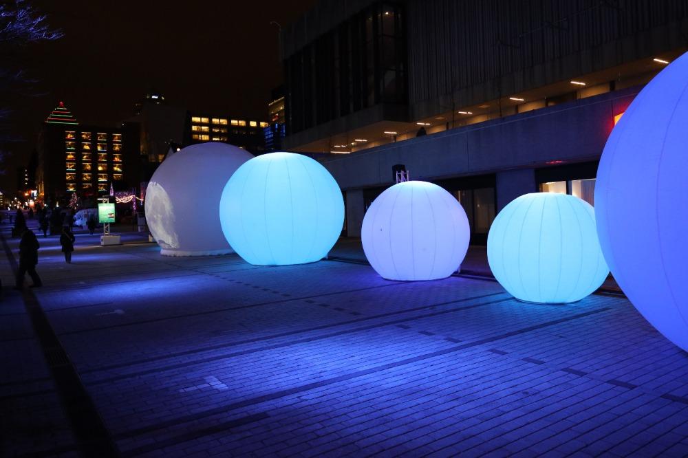Boules géantes illuminées en bleu pour l'installation Nouvelle Lune
