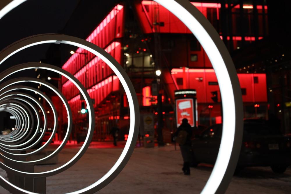 Cerceaux illuminées de l'installation Spectrum avec l'édifice 2-22 en arrière-plan